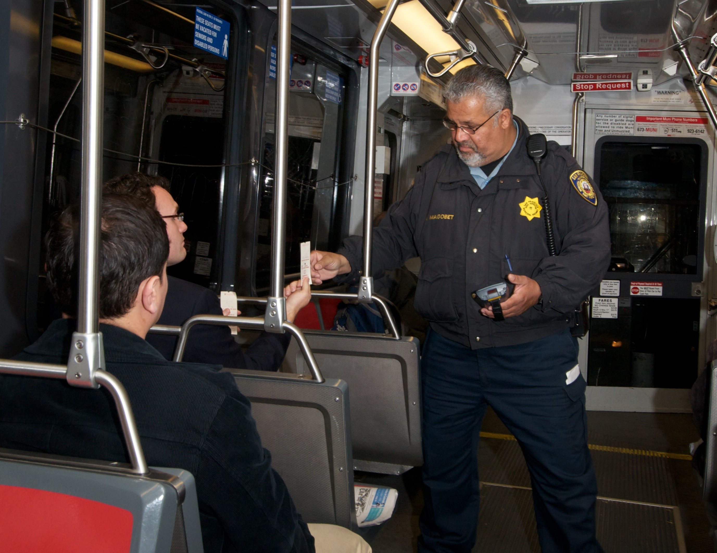 Fare control officer checking proof-of-payment tickets, San Francisco (credit: SFMTA)
