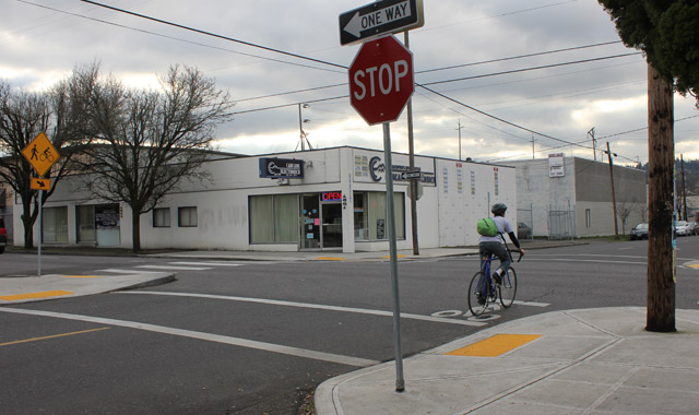Bicycle Forward Stop Bar - Portland, ORThis forward stop bar on the Clay Street Bicycle Boulevard allows bicyclist queuing beyond the pedestrian crossing to promote visibility of bicyclists and yielding by motorists.